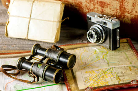 antique binoculars: vintage travel memories concept. Old camera, binoculars, letters and map holder with map