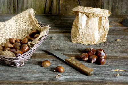 marron: sweet chestnuts in basket, paper bag and knife