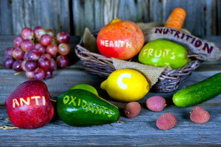 healthy nutrition: scattered fruits and vegetables with cut words - healthy lifestyle concept Stock Photo