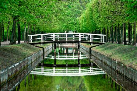 木製の白は、小さな川に架かる橋します。水面での反射 写真素材