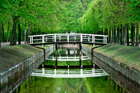 wooden white bridges over small river. Reflection at water surface
