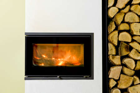 in insert: burning wood in fireplace insert. Wood stand with wood Stock Photo