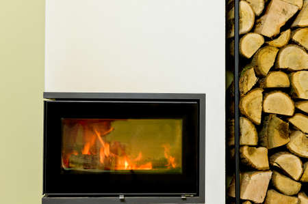 indoor inside: burning wood in wood stove. Wood stand with wood