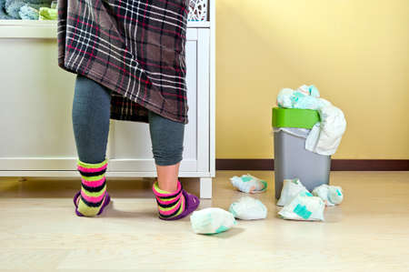 Woman in plaid skirt wearing blue tights and colourful socks changing babies diapers some used ones placed in a waste bucket and others around it on the floor. Stock Photo