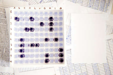 Laboratory battleship game made of defocused spectrophotometer cuvette in a box, syringes and paper sheets with filled in tables around it Stock Photo