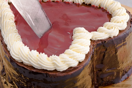 Chocolate cake in shape of a hearth is being cut Stock Photo