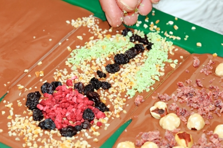 Chocolate with hazel nuts, strawberries and raisins is being made