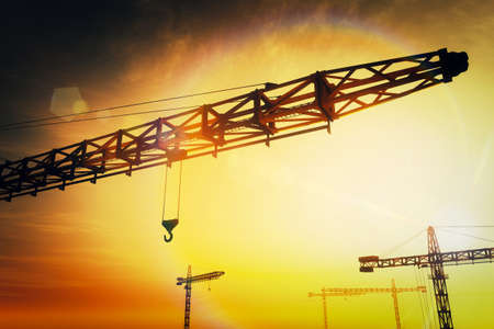 storage facility: Huge Construction Cranes in Industrial Zone in Sunset Sunrise 3D Artwork Concept of construction, heavy industry, commerce and architecture.