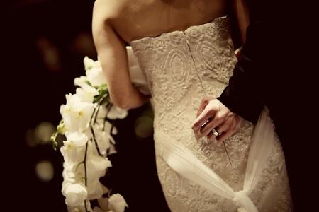 newlywed: Bride and groom standing behind the bride