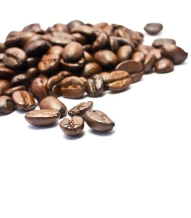 Los granos de café de cerca sobre fondo blanco