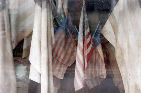 Faded and diry US flags in window of abandoned building