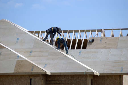 sheathing: Two roofers working on a new home