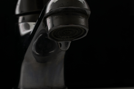 Water tap on black with water drop