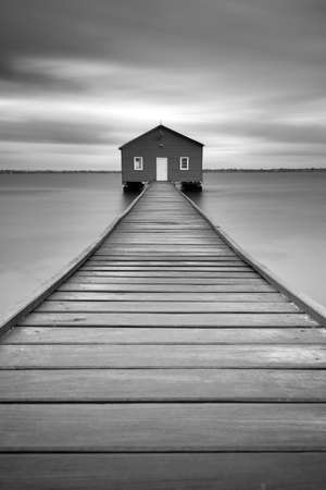 The Crawley Edge Boatshed. The blue boathouse on the Swan River with a wooden pier leading to the front door in Crawley, Perth, Western Australia