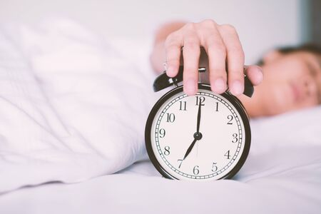 Woman sleep on the bed turns off the alarm clock wake up at the morning, Selective focus. Standard-Bild