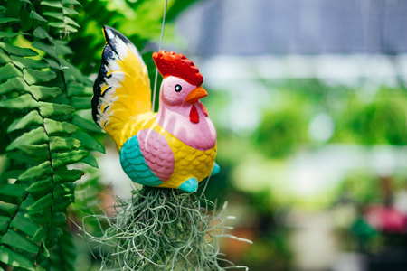 Colorful chicken doll hang on the metal rope in the garden.