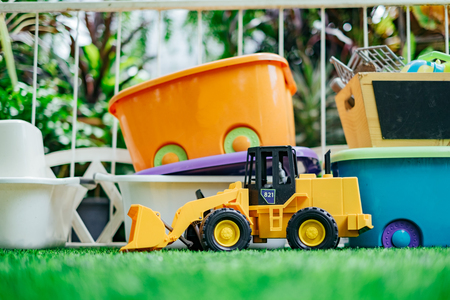 Tracktor toy car with toy boxes in the garden. Stock Photo