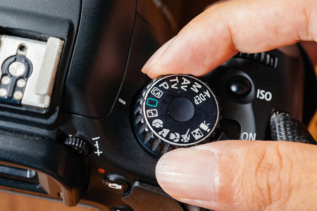 auto focus: Auto dial mode on dslr camera with fingers on the dial Stock Photo