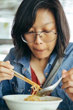 Women eating egg noodle with crispy pork from chopsticks and metal spoon