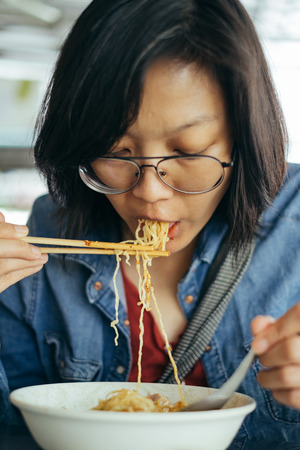 Women eating egg noodle with crispy pork from chopsticks and metal spoon.