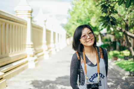 Woman tourist with camera smile in the thai temple. Stock Photo