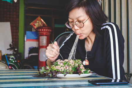 Woman eating spicy mince pork thai food on the wood table. Stock Photo