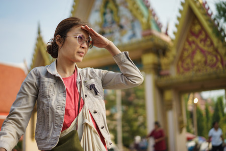 Asian woman looking toward for something with thai temple.
