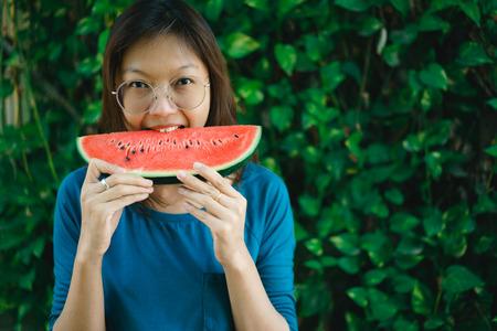 Asian Women biting Slice Of Watermelon. Stock Photo
