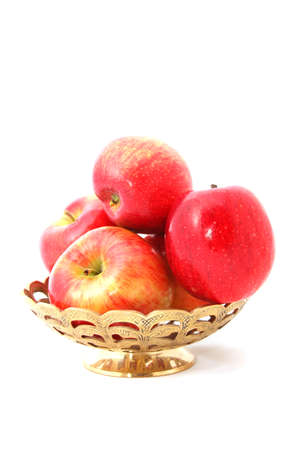 Apples in a gold engraved basket isolated on white