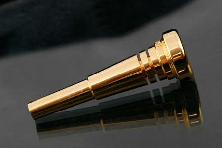 wind instrument: Gold plated trumpet mouthpiece on a shiny surface Stock Photo