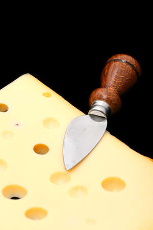 orifice: Cheese cut in slices on a black  Stock Photo