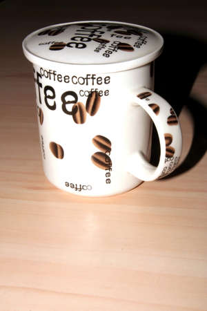 Coffee cup with coffee beans printed on its side on a wooden