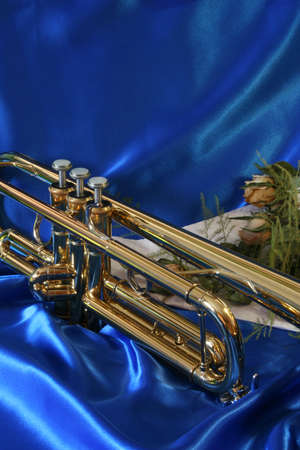 gold lacquer trumpet and old sere roses on blue satin  Stock Photo