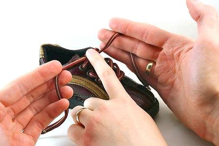 binding: Parents hands binding little baby shoelace Stock Photo
