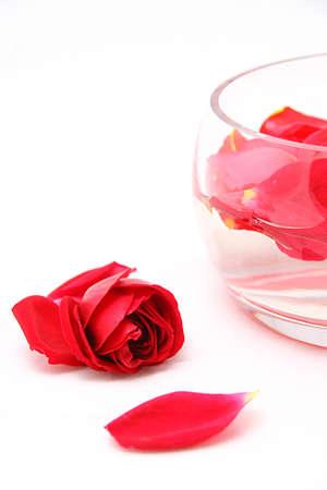 Petali di rose su un bianco in un vaso di vetro