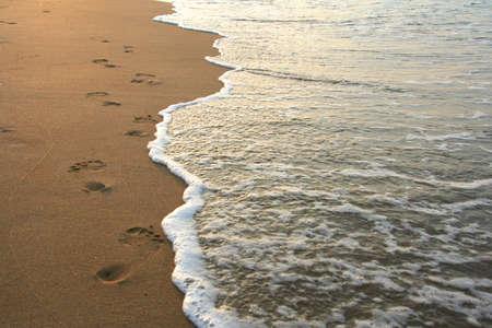 Stampe del piede sulla spiaggia di sabbia su sunrise