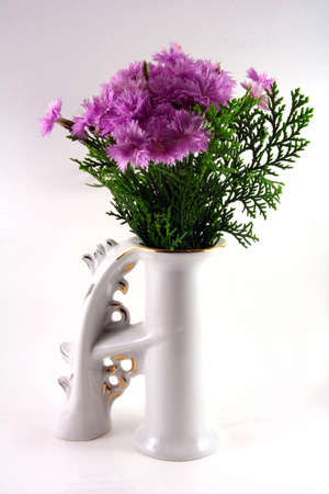 gillyflower: Violet dianthus in a white porcelain vase in letter shape Stock Photo