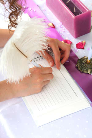 Notebook rosa e una penna penna su una tavola per gli ospiti di nozze Archivio Fotografico