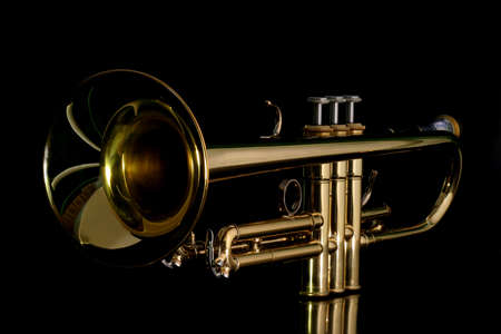 Gold lacquer trumpet with mouthpiece isolated on black Stock Photo