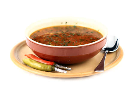 Close up of a beef soup plate and two peppers