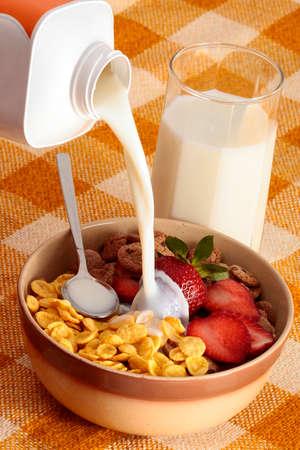 Versare latte cereali ciotola per la prima colazione come un concetto di cibo sano