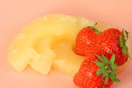Due fragola e tre fette di ananas close-up sul colore rosa Archivio Fotografico
