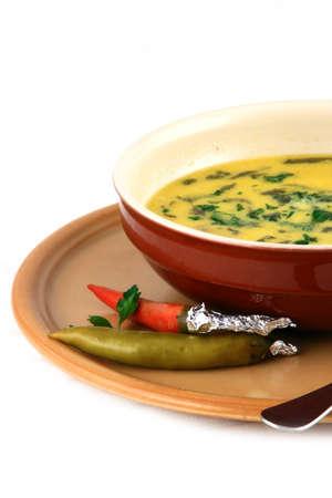Primo piano di un piatto di brodo di manzo e due peperoni