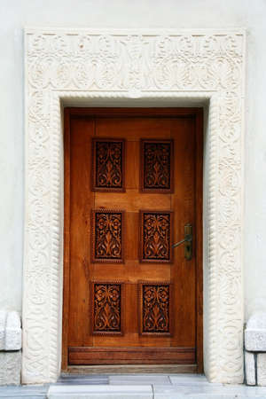 carved stone: Carved stone wall and wooden door in medieval style in romanian monastery