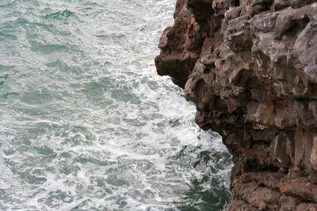 Stone coast and the sea splashing into the shore