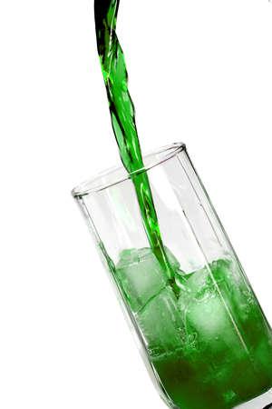 Aggiorna bevanda verde in un bicchiere con blocchi di ghiaccio Archivio Fotografico