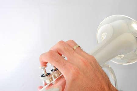 flugelhorn: Hand holding a silver fluegelhorn on grey