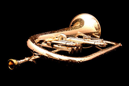 Wet fluegelhorn with golden mouthpiece isolated on black with water drops on it