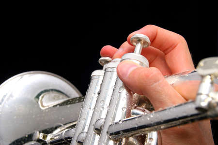 flugelhorn: hand holding a fluegelhorn on black with water drops on it Stock Photo