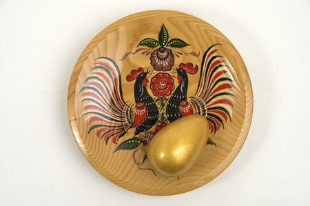 Colour wooden dish with figure and gold egg.